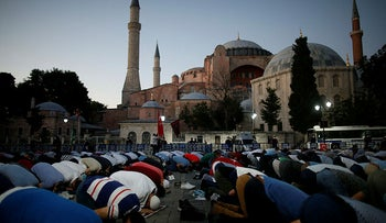 Muslims offer their evening prayers outside Hagia Sophia, Istanbul, following the decision to turn it back into a mosque, Friday, July 10, 2020.