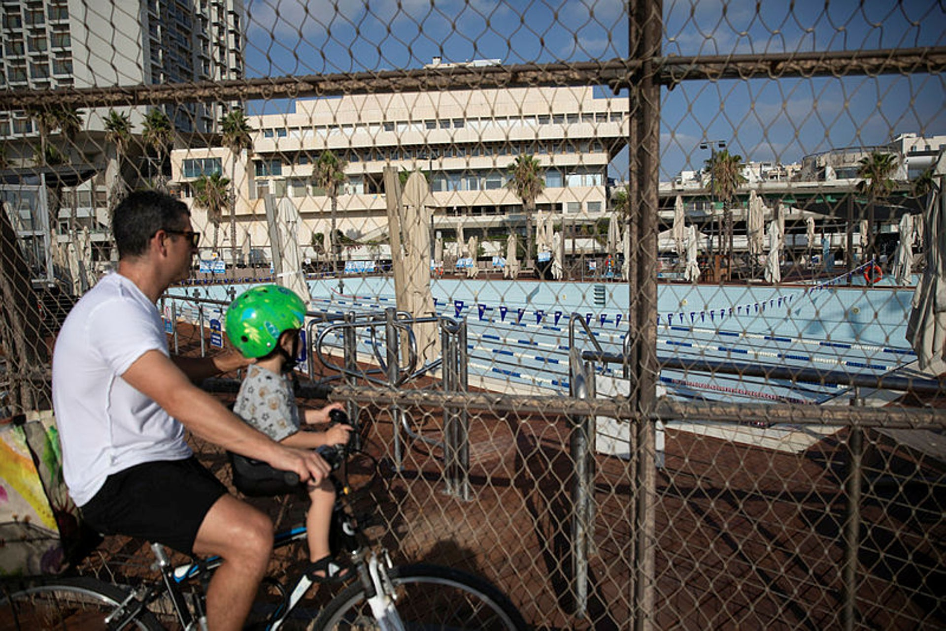 A man and his kid look into a closed pool, Tel Aviv, July 13, 2020.