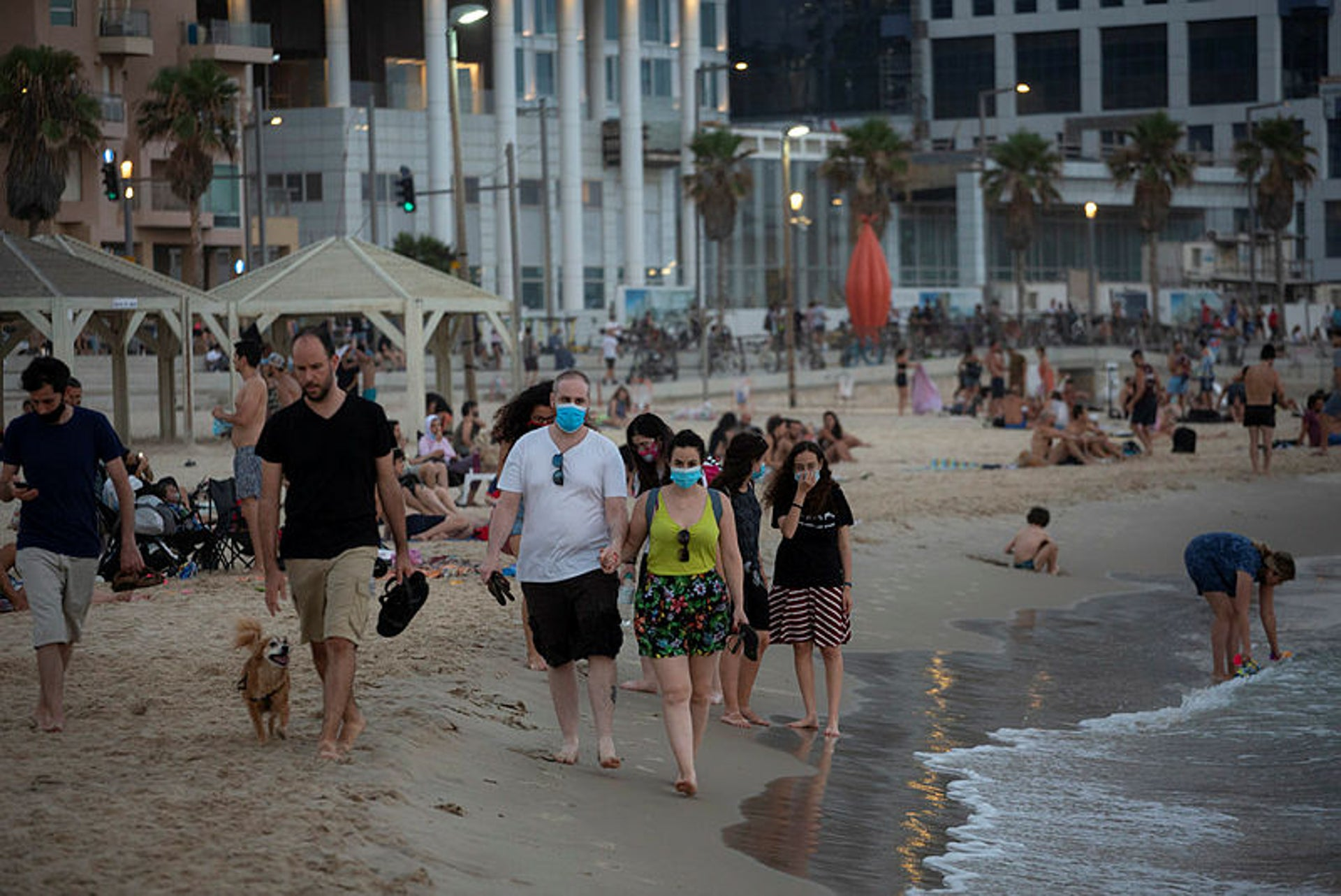 People wearing face masks walk by the beach, Tel Aviv, July 16, 2020.