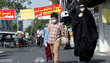 An Iranian woman and her son wearing a protective face mask walks the street, following the outbreak of the coronavirus, Tehran, June 28, 2020