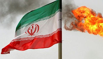 A gas flare on an oil production platform in the Soroush oil fields is seen alongside an Iranian flag in the Gulf, July 25, 2005.