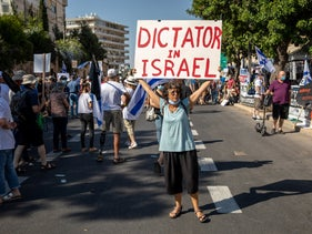 A protester holds a sign that reads 'dictator of Israel,' Jerusalem, July 3, 2020