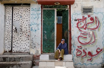 A Palestinian woman sits outside her home in Jabalya refugee camp in the northern Gaza Strip, May 5, 2020.