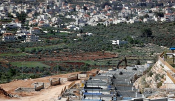 The Palestinian village of Turmus Ayya in the background and houses under construction in the Jewish settlement of Shilo in the occupied West Bank between Ramallah and Nablus, March 31, 2017.