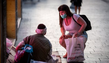 A woman speaks to a panhandler in Jerusalem on July 19, 2020.