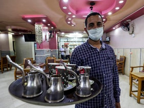 A waiter carries an order at a cafe in the Egyptian capital Cairo on June 27, 2020.