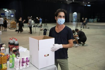 Singer Aviv Geffen distributes food in Tel Aviv to Israelis who have been put out of work in the cultural sector.