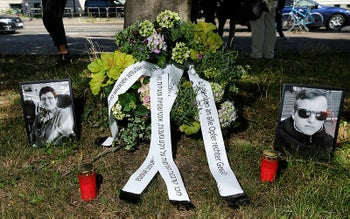 Candles, a funeral wreath and pictures of the victims of the terrorist attack in Halle stand on a green area in front of the Magdeburg, Germany, July 21, 2020.