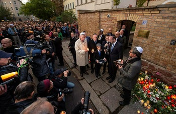 People pray together with Jewish people in front of the synagogue during the Sabbath celebrations in Halle, Germany, October 11, 2019.
