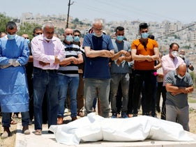Relatives pray before the body of a Palestinian man who has died after contracting the coronavirus, Hebron, July 5, 2020.