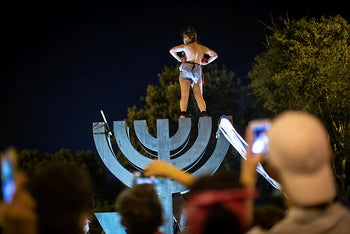 A woman stands on top of a Menorah and takes her shirt off in protest at the Jerusalem demonstration, July 19, 2020.