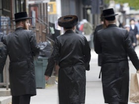 Three Hasidic Jews walking down the street in Williamsburg, Brooklyn, in pre-coronavirus times.