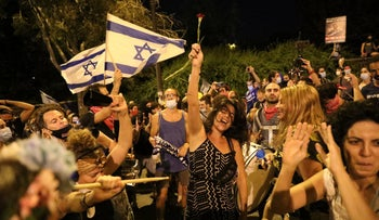 Protesters wave Israeli flags at a demonstration in Jerusalem, July 21, 2020.