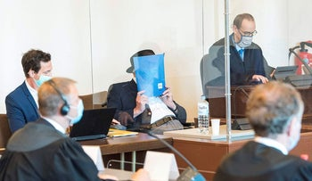 Bruno Dey (C), a former SS-watchman at the Stutthof concentration camp, hides his face behind a folder next to his lawyer Stefan Waterkamp (R) and a doctor (L) at the start of a hearing in his trial on July 23, 2020 in Hamburg, northern Germany