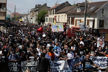 """Demonstrators holding a placard reading """"Generation Adama-Climate, we want to breathe"""" take part of a march to mark the fourth anniversary of the death of Adama Traore, a Black man in police custody, in Beaumont Sur Oise, north suburb of Paris, July 18, 2020."""