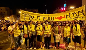 """The """"wall of moms"""" holding a banner in Jerusalem stating """"Mom will protect you,"""" July 25, 2020."""