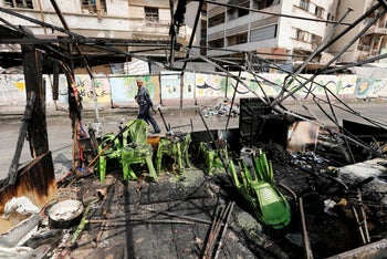 A man walks past the remains of a tent, which was burnt last night during the ongoing anti-government protest in Baghdad, on July 27, 2020.