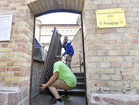 Carpenter Thomas Thiele, front, removes the bullet hole-ridden door of synagogue in Halle, Germany, July 28, 2020.