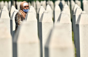 A Bosnian Muslim woman, survivor of the 1995 Srebrenica massacre, walks between tombstones at the Potocari memorial cemetery, just outside Srebrenica, Bosnia. July 11, 2020