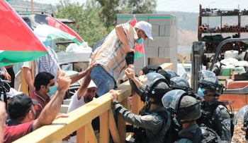 Israeli border guards stop a Palestinian demonstrator from crossing a barrier during a rally to protest the plan to annex parts of the occupied West Bank, Haris, West Bank, July 24, 2020.