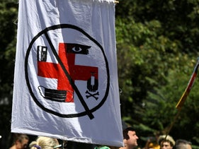 A demonstrator holds a banner during a protest against the government's restrictions amid the coronavirus disease, in Berlin, Germany, August 1, 2020.