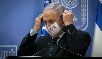Prime Minister Benjamin Netanyahu putting on a face mask at his office in Jerusalem, June 30, 2020.