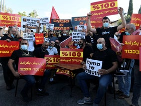 Protesters at a demonstration calling on the Israeli government to compensate workers made unemployed due to the coronavirus crisis, in Haifa on July 21, 2020.