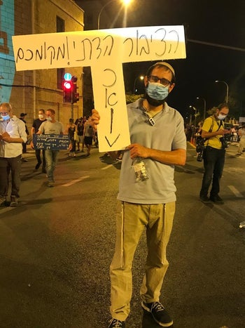 "Rabbi Avidan Freedman attending the protest outside Prime Minister Benjamin Netanyahu's residence in Jerusalem, July 30, 2020. He's holding a sign that reads: ""Religious public: Your place is here."""