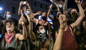 Anti-government protesters march outside the prime minister's residence in Jerusalem, August 1, 2020.