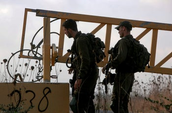 IDF soldiers man a position on a road leading to the Syrian border, near the location where the army said it killed four men laying explosives at a security fence, on August 3, 2020.