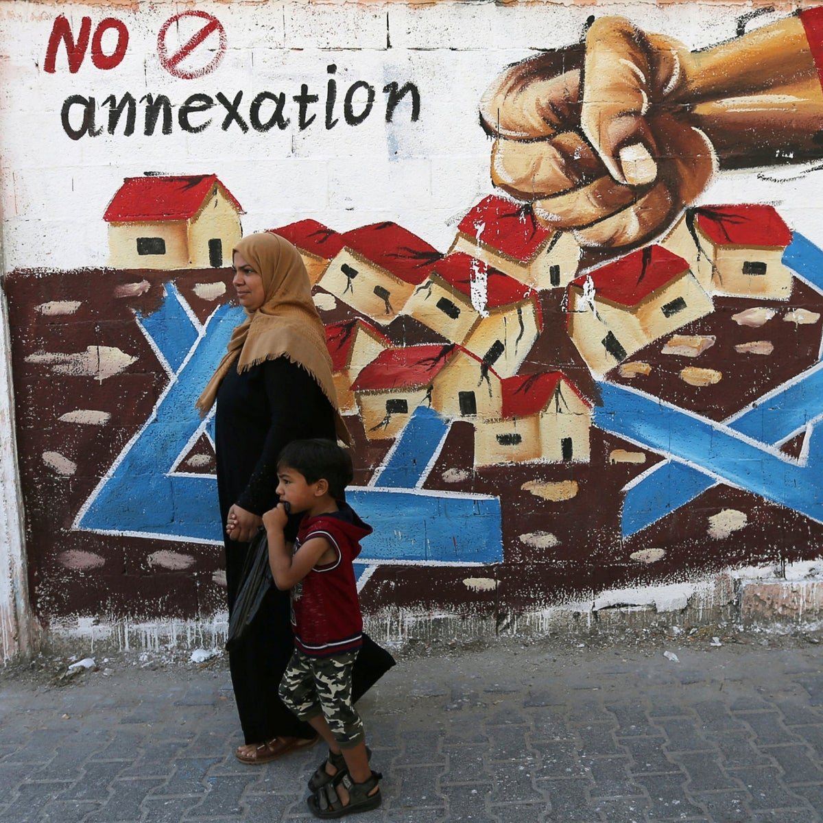 A Palestinian woman walking with her son past a mural protesting Israel's plan to annex parts of the West Bank, Rafah, Gaza Strip, July 14, 2020.