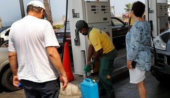 Lebanese citizens look at a gas station worker, center, fills gasoline on their jerry can to power their home generator, Beirut, July 29, 2020