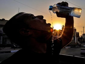 Laith Jabbar, a gas station worker drinks water in Basra, Iraq, July. 27, 2020.