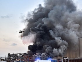 A helicopter puts out a fire at the scene of an explosion at the port of Lebanon's capital Beirut on August 4, 2020.