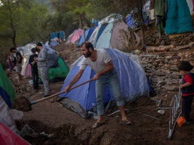 A Syrian man shovels dirt next to his tent near the refugee and migrant camp at the Greek island of Samos island, in 2019.