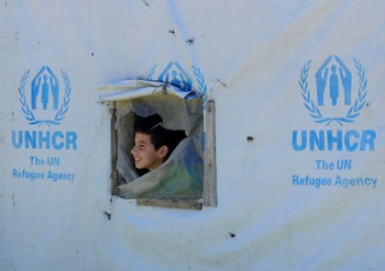 A Syrian refugee boy looks out from a tent window at a Syrian refugee camp in the Bekaa valley, Lebanon May, 2020.