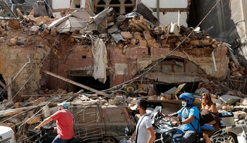 Citizens ride their scooters and motorcycles in front of a house that was destroyed in Tuesday's massive explosion in the seaport of Beirut, Lebanon, Wednesday, August 5, 2020.