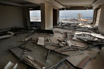 The scene of the explosion that hit the seaport of Beirut is seen through a damaged apartment in Beirut, Lebanon, Wednesday, August 5, 2020.