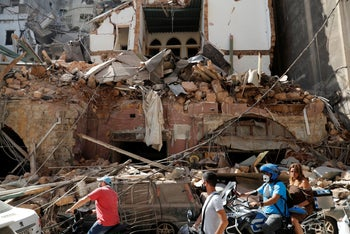Citizens ride their scooters and motorcycles in front of a house that was destroyed in Tuesday's massive explosion in the seaport of Beirut August 5, 2020.