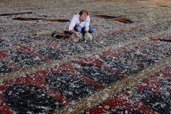 A man removes broken glass scattered on the carpet of a mosque damaged in Tuesday's blast in Beirut, August 5, 2020