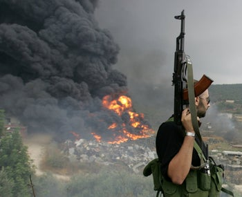 FILE PHOTO: A Lebanese Hezbollah guerrilla looks at a fire rising from a burning object in a Beirut suburb, Lebanon July 17, 2006.