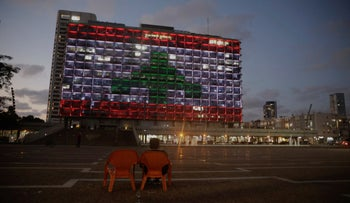 An Israeli woman sits as the municipality building is illuminated with the Lebanese flag In Tel Aviv, Israel, August 5, 2020.