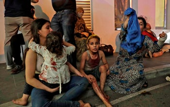 Wounded people wait to received help outside a hospital following an explosion in the Lebanese capital Beirut on August 4, 2020.