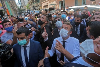 Macron chats with people as he visits the Gemmayzeh neighborhood which has suffered extensive damage due to a massive explosion in the Lebanese capital, on August, 6. 2020.