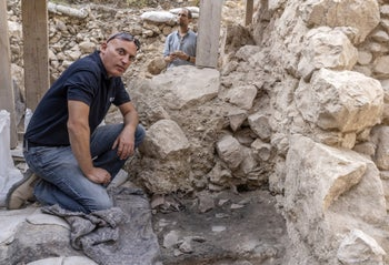 Dr Yiftah Shalev by the smashed pottery from First Temple period at the site