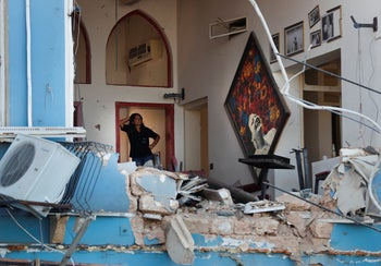 A woman stands inside a damaged restaurant a day after an explosion hit the seaport of Beirut, Lebanon, August 5, 2020.