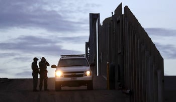 United States Border Patrol agents stand by a vehicle near one of the border walls separating Tijuana, Mexico and San Diego, in San Diego, November 21, 2018.