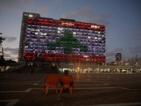 An Israeli woman sits as the municipality building is illuminated with the Lebanese flag In Tel Aviv, August 5, 2020.