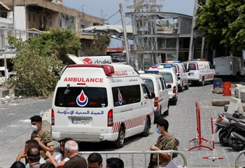 Civil defense ambulances from Hezbollah enter the site of the explosion that hit the seaport of Beirut, August 6, 2020