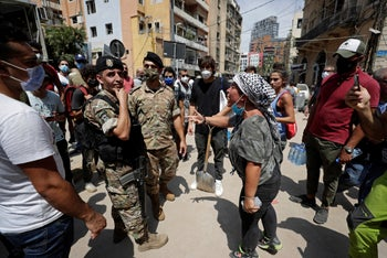 A woman yells at Lebanese soldiers as French President Emmanuel Macron visits the Gemmayzeh neighborhood, which suffered extensive damage from the explosion, August 6, 2020.